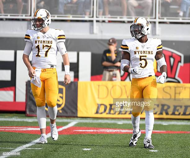 Quarterback Josh Allen and running back Brian Hill of the Wyoming Cowboys walk on the field during their game against the UNLV Rebels at Sam Boyd...