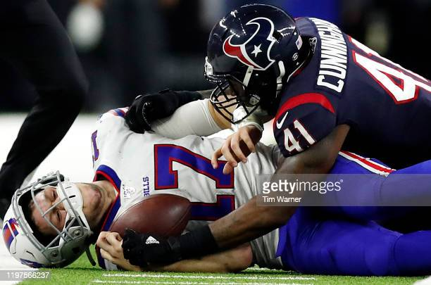 Quarterback Josh Allen of the Buffalo Bills is tackled by inside linebacker Zach Cunningham of the Houston Texans during the AFC Wild Card Playoff...
