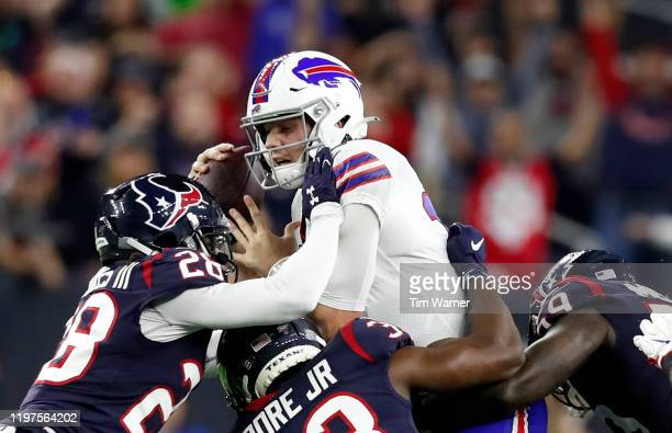 Quarterback Josh Allen of the Buffalo Bills is tackled by the defense of the Houston Texans during the AFC Wild Card Playoff game at NRG Stadium on...