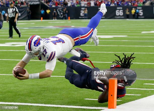 Quarterback Josh Allen of the Buffalo Bills leaps over Jahleel Addae of the Houston Texans for a touchdown on a pass from John Brown in the first...