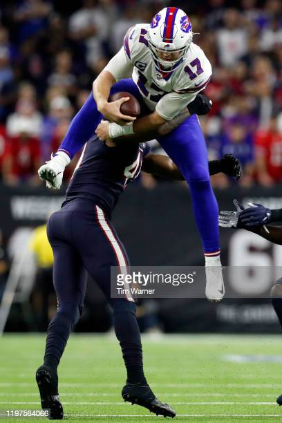 Quarterback Josh Allen of the Buffalo Bills leaps over linebacker Zach Cunningham of the Houston Texans during the AFC Wild Card Playoff game at NRG...