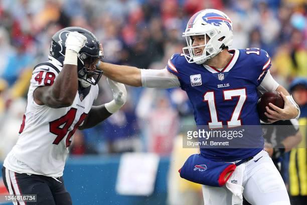 Quarterback Josh Allen of the Buffalo Bills straight arms Joe Thomas of the Houston Texans in the first quarter at Highmark Stadium on October 03,...