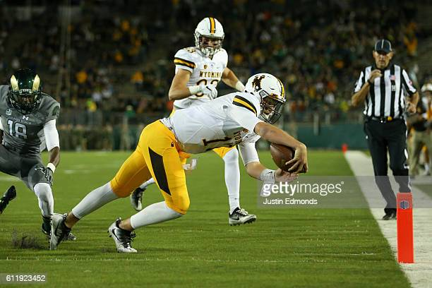 Quarterback Josh Allen of the Wyoming Cowboys dives into the end zone past the defense of defensive back Braylin Scott of the Colorado State Rams on...