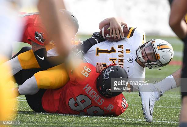 Quarterback Josh Allen of the Wyoming Cowboys is tackled by defensive lineman Mike Hughes Jr #99 of the UNLV Rebels during their game at Sam Boyd...
