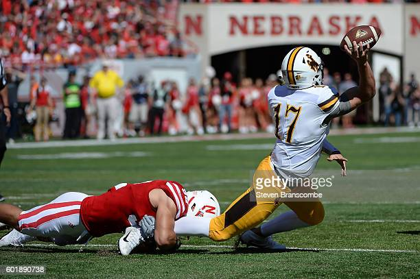 Quarterback Josh Allen of the Wyoming Cowboys passes out of the hold from linebacker Josh Banderas of the Nebraska Cornhuskers at Memorial Stadium on...
