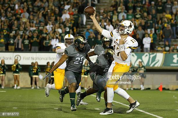 Quarterback Josh Allen of the Wyoming Cowboys throws a pass under pressure from the Colorado State Rams defense during the first quarter at Sonny...