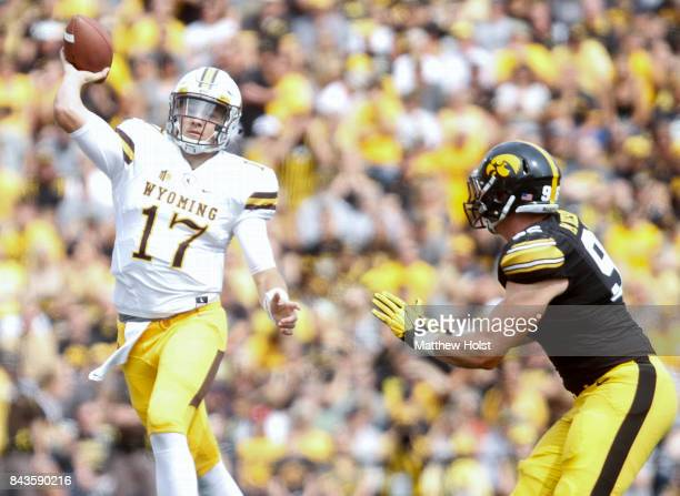 Quarterback Josh Allen of the Wyoming Cowboys throws pass in front of defensive end Matt Nelson of the Iowa Hawkeyes during the second quarter on...