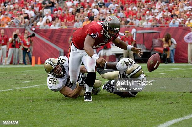 Quarterback Josh Freeman of the Tampa Bay Buccaneers is sacked by Scott Fujita and Charles Grant of the New Orleans Saints and fumbles the ball...