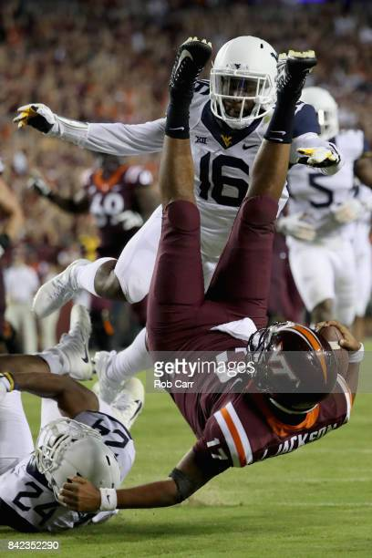 Quarterback Josh Jackson of the Virginia Tech Hokies is tackled short of the goal line by Toyous Avery and cornerback Hakeem Bailey of the West...