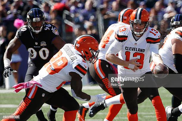 Quarterback Josh McCown of the Cleveland Browns hands the ball off to running back Duke Johnson of the Cleveland Browns while linebacker Za'Darius...