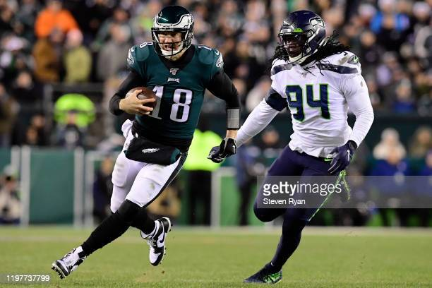 Quarterback Josh McCown of the Philadelphia Eagles runs for a first down over Ezekiel Ansah of the Seattle Seahawks during the NFC Wild Card Playoff...