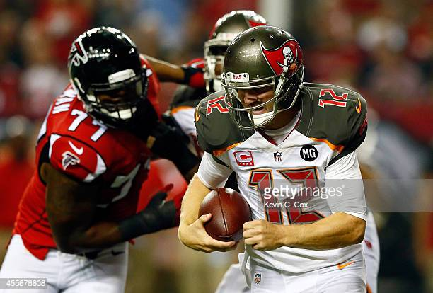 Quarterback Josh McCown of the Tampa Bay Buccaneers scrambles under pressure from defensive end Ra'Shede Hageman of the Atlanta Falcons during a game...
