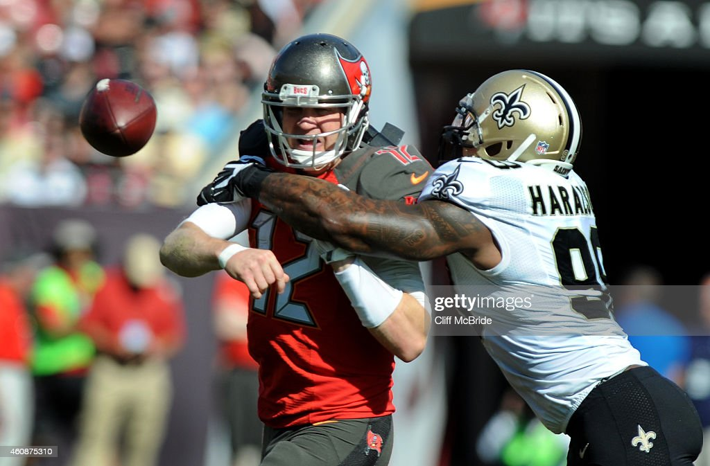 Quarterback Josh McCown #12 of the Tampa Bay Buccaneers throws the ball as he is hit by outside linebacker Parys Haralson #98 of the New Orleans Saints in the first quarter at Raymond James Stadium on December 28, 2014 in Tampa, Florida.