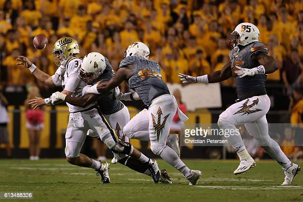 Quarterback Josh Rosen of the UCLA Bruins fumbles the football as he is tackled by defensive lineman Koron Crump of the Arizona State Sun Devils...