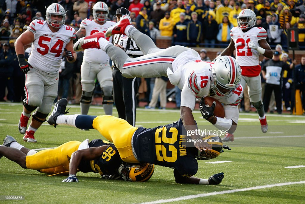 Quarterback J.T. Barrett #16 of the Ohio State Buckeyes dives over Jarrod Wilson #22 and Jourdan Lewis #26 of the Michigan Wolverines for a third quarter touchdown at Michigan Stadium on November 28, 2015 in Ann Arbor, Michigan.