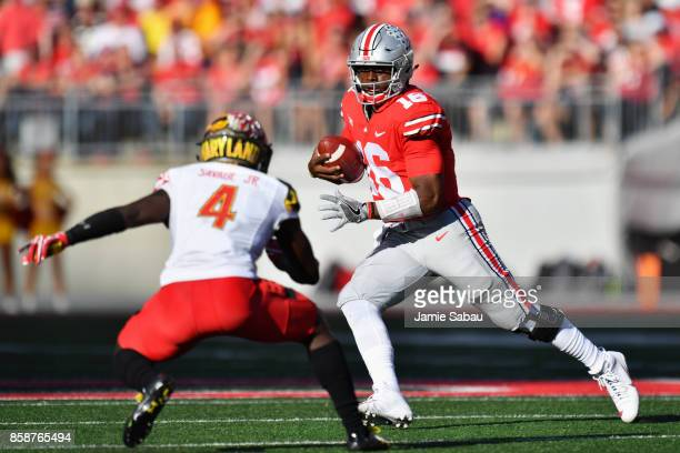 Quarterback JT Barrett of the Ohio State Buckeyes looks for running room in the first quarter as Darnell Savage Jr #4 of the Maryland Terrapins...