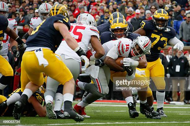 Quarterback J.T. Barrett of the Ohio State Buckeyes rushes for a first quarter touchdown against the Michigan Wolverines at Michigan Stadium on...
