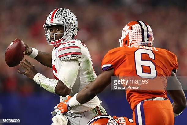 Quarterback JT Barrett of the Ohio State Buckeyes scrambles to pass pressured by linebacker Dorian O'Daniel of the Clemson Tigers during the...