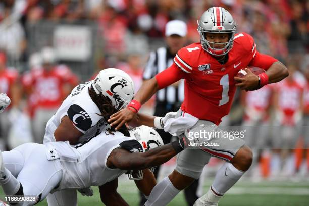 Quarterback Justin Fields of the Ohio State Buckeyes eludes the tackle attempts of Bryan Wright and Arquon Bush of the Cincinnati Bearcats while...