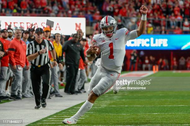 Quarterback Justin Fields of the Ohio State Buckeyes runs down the sidelines against the Nebraska Cornhuskers at Memorial Stadium on September 28...