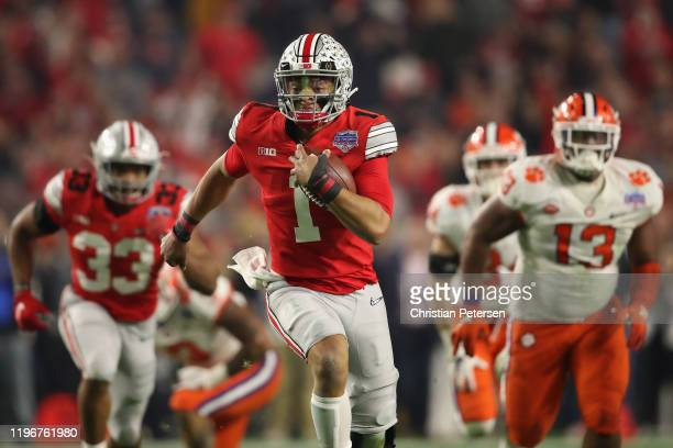 Quarterback Justin Fields of the Ohio State Buckeyes scrambles with the football during the PlayStation Fiesta Bowl against the Clemson Tigers at...