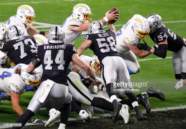 Quarterback Justin Herbert of the Los Angeles Chargers dives into the end zone for a touchdown to win the game 30-27 during overtime against the Las...