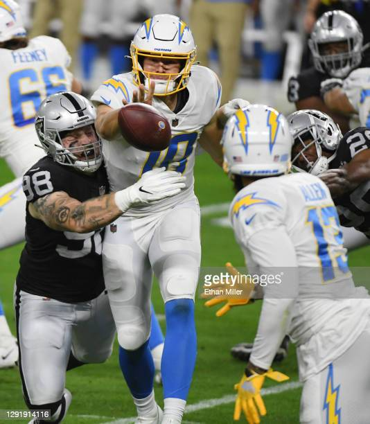 Quarterback Justin Herbert of the Los Angeles Chargers pitches the ball to the wide receiver Keenan Allen under pressure from defensive end Maxx...