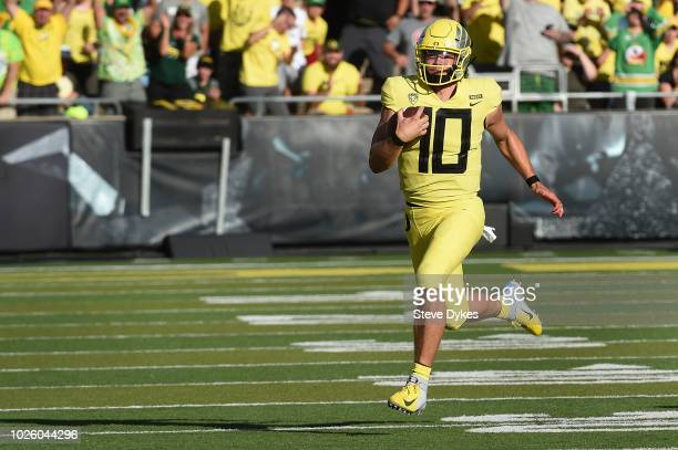 Quarterback Justin Herbert of the Oregon Ducks breaks out intot the open on a run during the first quarter of the qame against the Bowling Green...
