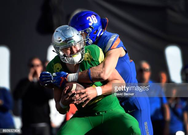 Quarterback Justin Herbert of the Oregon Ducks is sacked by Leighton Vander Esch of the Boise State Broncos during the first half of the Las Vegas...