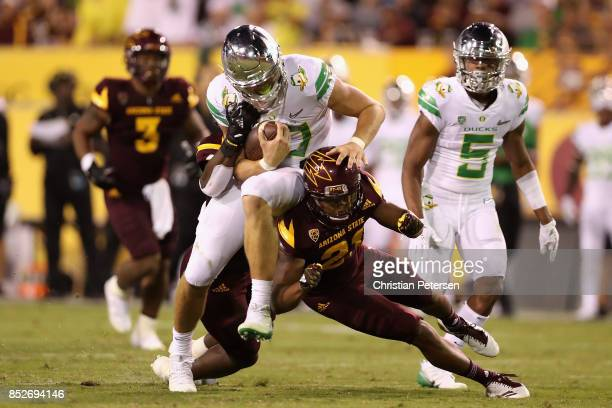 Quarterback Justin Herbert of the Oregon Ducks is tackled by defensive back Chad Adams of the Arizona State Sun Devils as he scrambles with the...