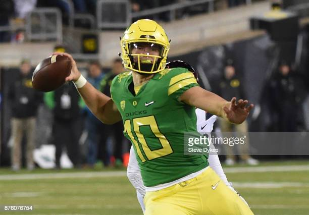 Quarterback Justin Herbert of the Oregon Ducks passes the ball as defensive end Jack Banda of the Arizona Wildcats applies pressure during the second...