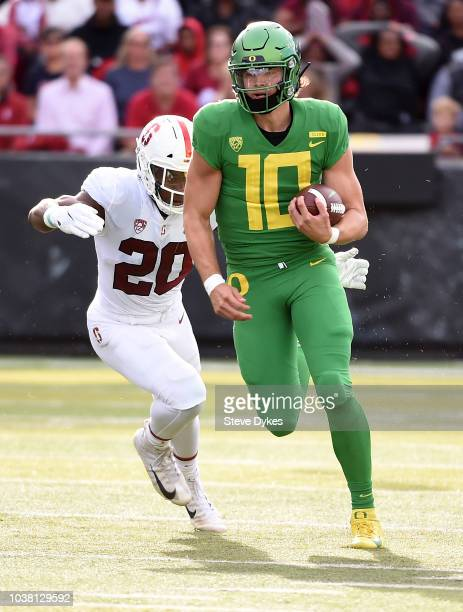 Quarterback Justin Herbert of the Oregon Ducks runs past linebacker Bobby Okereke of the Stanford Cardinal during the first quarter of the game at...