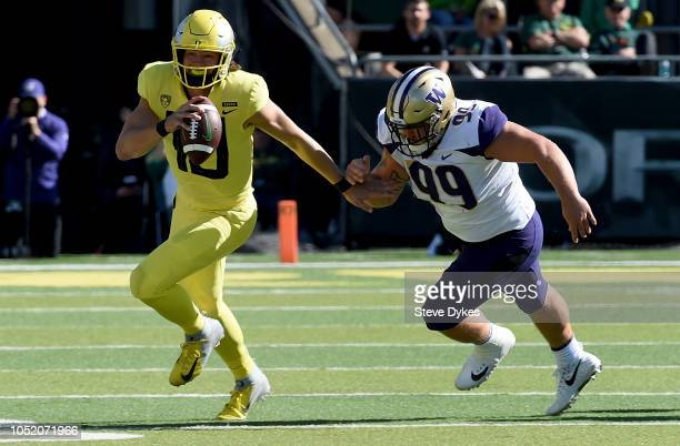 Quarterback Justin Herbert of the Oregon Ducks scrambles against defensive lineman Greg Gaines of the Washington Huskies in the first half of the...