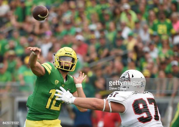 Quarterback Justin Herbert of the Oregon Ducks throws a touchdown pass as defensive lineman Robert Torgerson of the Southern Utah Thunderbirds...