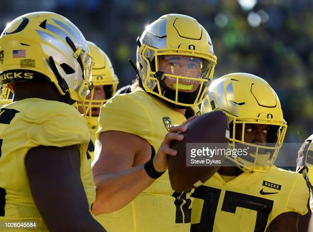 Quarterback Justin Herbert of the Oregon Ducks tosses the ball to an official afterscoring touchdown during the second quarter of the qame against...