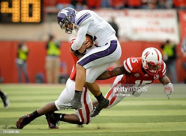 Quarterback Kain Colter of the Northwestern Wildcats takes a shot from linebacker Lavonte David and cornerback Alfonzo Dennard of the Nebraska...