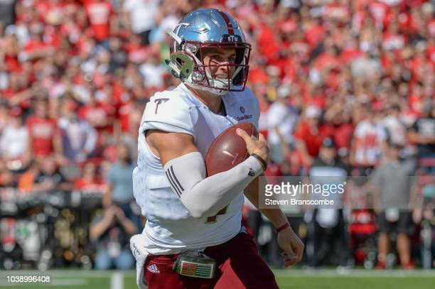 Quarterback Kaleb Barker of the Troy Trojans rolls out to pass in the first half against the Nebraska Cornhuskers at Memorial Stadium on September 15...