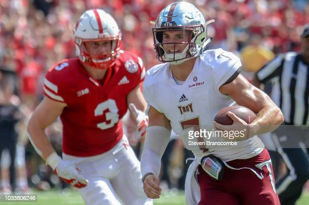 Quarterback Kaleb Barker of the Troy Trojans runs from linebacker Will Honas of the Nebraska Cornhuskers in the second half at Memorial Stadium on...