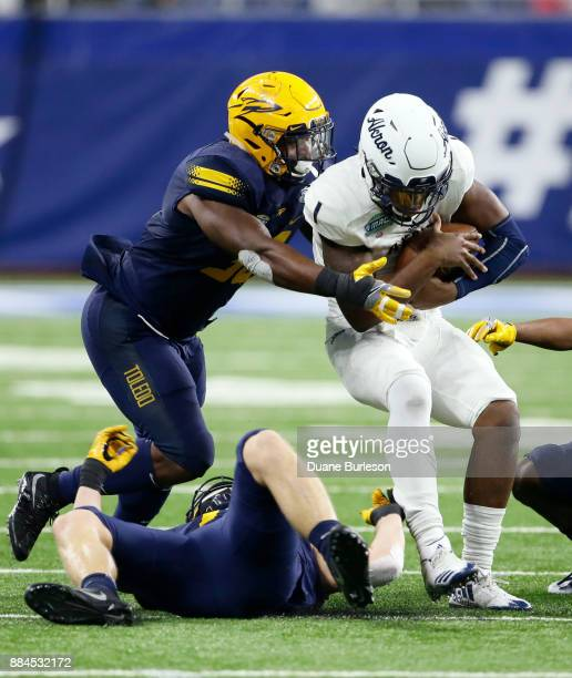 Quarterback Kato Nelson of the Akron Zips is tackled by linebacker Ja'Wuan Woodley of the Toledo Rockets during the first half at Ford Field on...