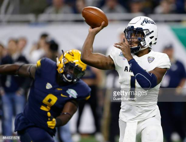Quarterback Kato Nelson of the Akron Zips passes the ball as defensive end Olasunkanmi Adeniyi of the Toledo Rockets closes in during the first half...
