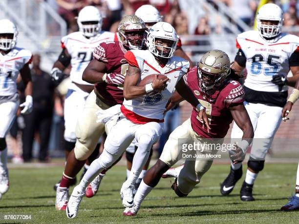 Quarterback Keenan Black of the Delaware State Hornets avoids being tackled by Defensive End Josh Sweat of the Florida State Seminoles during the...