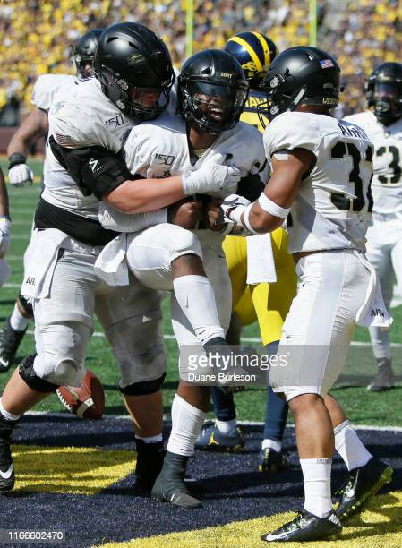 Quarterback Kelvin Hopkins Jr #8 of the Army Black Knights celebrates his six yard touchdown run with offensive lineman Peyton Reeder and running...