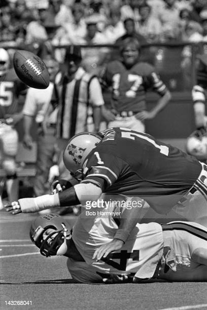 Quarterback Ken Anderson of the Cincinnati Bengals grimaces as he is sacked and fumbles the ball against Ray Hamilton of the New England Patriots on...