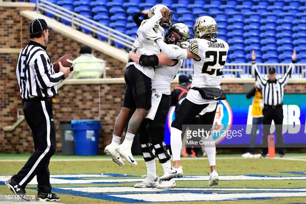 Quarterback Kendall Hinton celebrates with wide receiver James Sriraman and offensive lineman Allan Rappleyea of the Wake Forest Demon Deacons after...