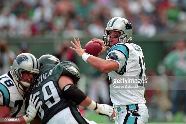 Quarterback Kerry Collins of the Carolina Panthers passes as offensive lineman Blake Brockermeyer blocks defensive lineman Mike Mamula of the...