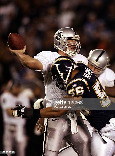 Quarterback Kerry Collins of the Oakland Raiders throws the ball as he is hit by Linebacker Shawne Merriman of San Diego Chargers during the 2nd half...