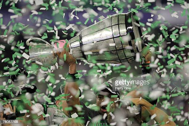 Quarterback Kerry Joseph of the Saskatchewan Rough Riders hoists the trophy as confetti falls in celebration of a 23-19 victory over the Winnipeg...