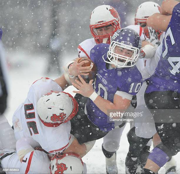 Quarterback Kevin Burke of the Mount Union Purple Raiders is tackled by linebacker Nick Samuelson of the North Central Cardinals during a game...