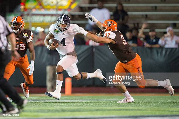Quarterback Kevin Ellison of the Georgia Southern Eagles looks to avoid a tackle by defensive lineman Terrance Bush of the Bowling Green Falcons on...
