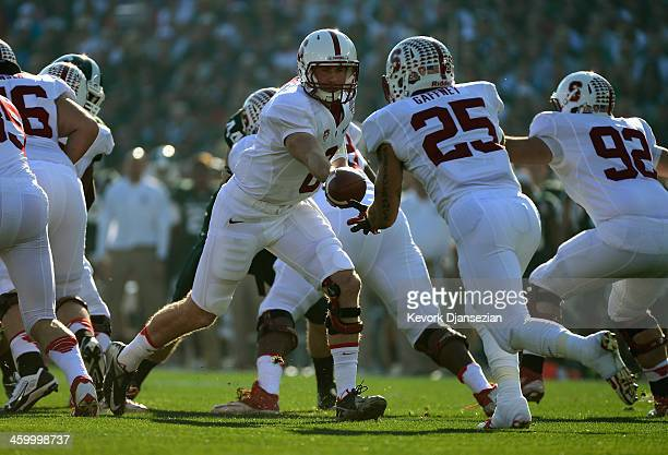 Quarterback Kevin Hogan hands the ball off to running back Tyler Gaffney of the Stanford Cardinal against the Michigan State Spartans during the...